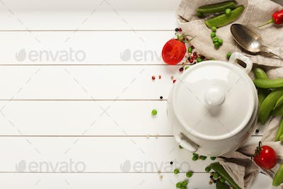 White cooking pot and ingredients for soup or stew