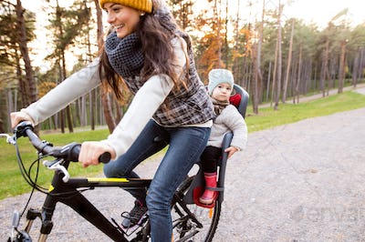 Young mother and daughter cycling in autumn park