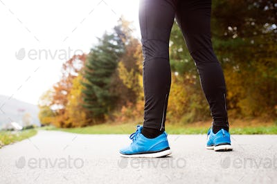 Legs of unrecognizable runner standing on concrete path,close up
