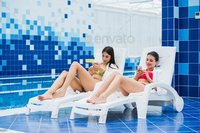 Young girls friends messaging with friend on her smartphone. Relaxation spa and technology social