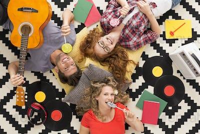 Happy friends eating lollipops surronded by vinyls