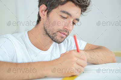 Man at desk with ruler and pencil