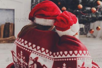 Children in santa hats near christmas tree, wait for holidays
