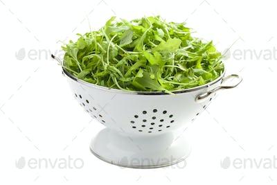 arugula leaves in white colander