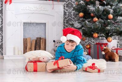 Cute boy in santa hat unwrapping christmas presents