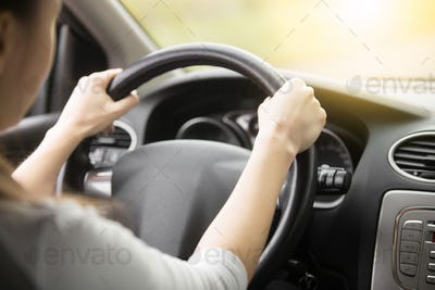Close-up of female hands on the steering wheel