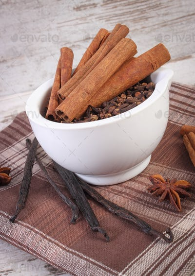 Fragrant cloves and cinnamon in mortar and spices on rustic board
