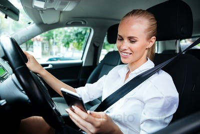 Smiling business woman dialing phone number while driving car