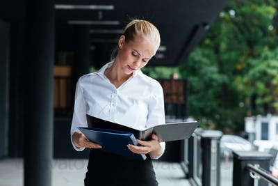 Smiling businesswoman standing with folders