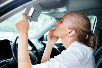 Pretty young business woman looking in mirror while driving car