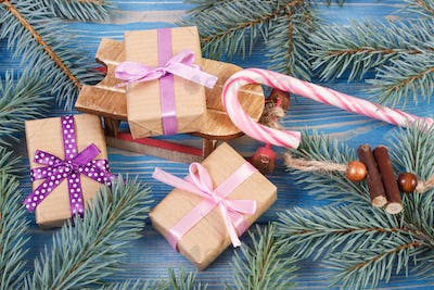 Wooden sled and wrapped gifts with ribbons for Christmas, spruce branches
