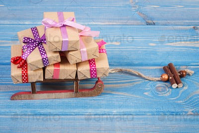 Wooden sled and wrapped gifts with ribbons for Christmas or other celebration