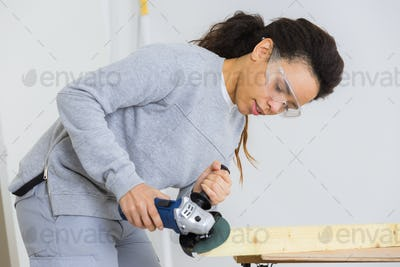 young adult female worker grinding plank with electric grinder