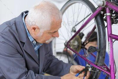 man repairing bike gear in his workshop