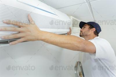 tech guy carefully installing new ac