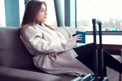 Businesswoman sitting in front of airport window