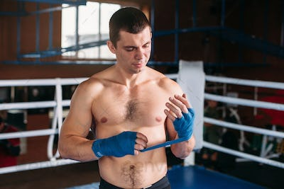 Boxer pulls bandage before the fight or training.