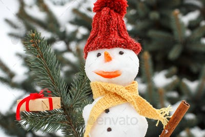 Decorated snowman with gift for Christmas, background of coniferous tree covered snow