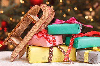 Colorful wrapped gifts with wooden sled and christmas tree with lights in background