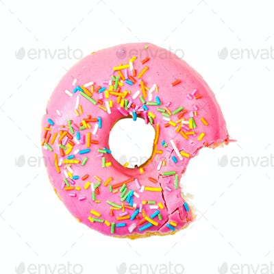 Bitten strawberry donut with colorful sprinkles. Top view.