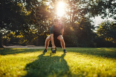 Fit young man exercising with kettlebell outdoors