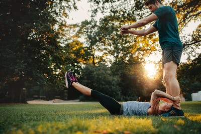 Woman stretching with support from personal trainer