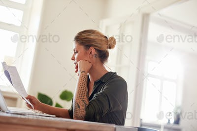 Woman going through contract papers at home office