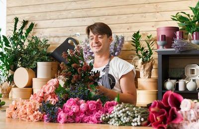 Man florist assistant in flower shop delivery make rose bouquet