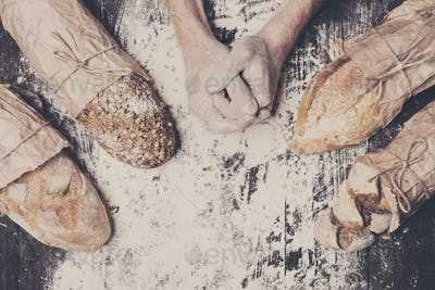 Bakery concept background. Hands and sorts of bread loaf