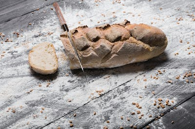 Bakery concept background. Knife cutting bread loaf slices