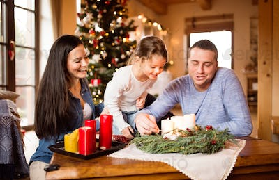 Young family lighting candles on advent wreath. Christmas tree.