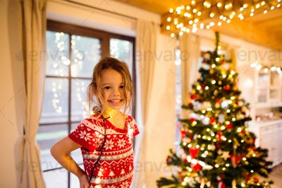 Little girl decorating Christmas tree tangled in chain lights.