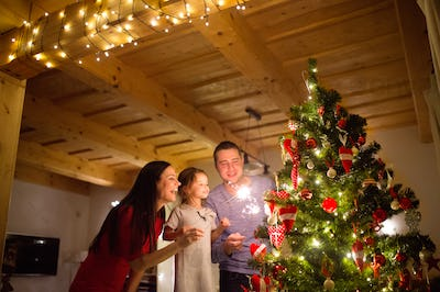 Young family with sparklers at Christmas tree at home.