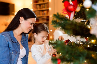 Young mother with daugter decorating Christmas tree together.