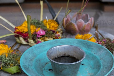Religious offerings in Bali, colored flowers with turquoise dish