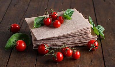 Raw lasagna sheets, basil and cherry tomatoes