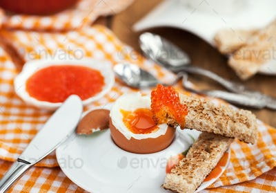 Boiled egg with red caviar, toast and coffee