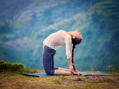 Woman doing yoga asana Ustrasana camel pose outdoors