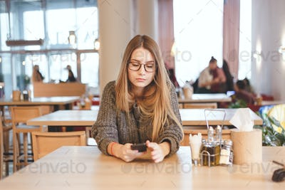 Portrait of cute freelancer girl sitting in a cafe. She wears brown hipster eyeglasses.