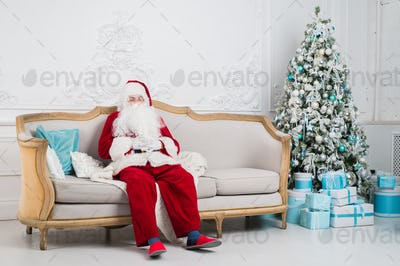 Traditional Santa Claus sitting on the couch and having a rest. Christmas. Red background.