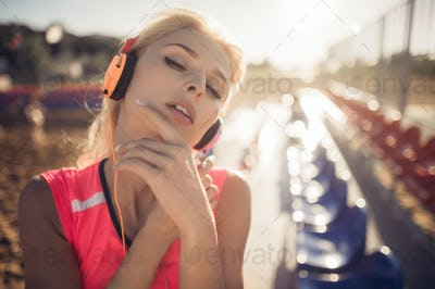 Young beautiful woman with headphones posing over beach volley seats