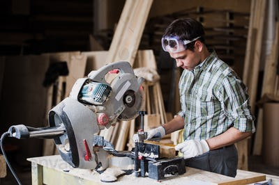 Skilled carpenter cutting a piece of wood in his woodwork workshop, using circular saw with other