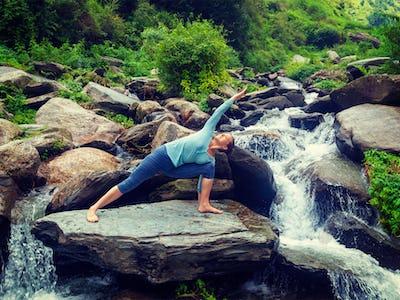 Woman practices yoga asana Utthita Parsvakonasana outdoors