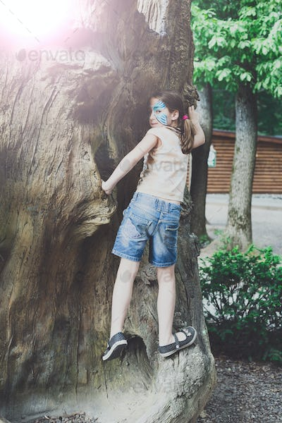 Girl child outdoors climb tree with butterfly face painting