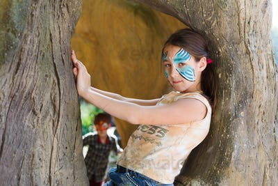 Girl child outdoors in tree with butterfly face painting