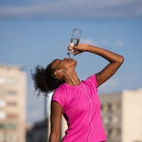 african american woman drinking water after jogging