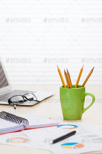 Office workplace with laptop, reports and pencils