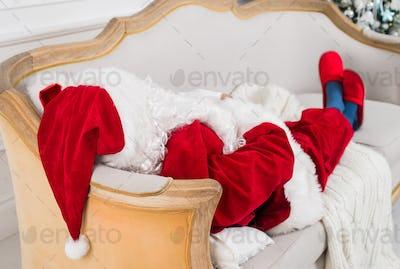 Santa Claus resting on a sofa at home.