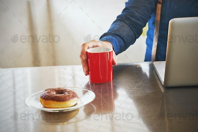 Architect man having breakfast while working at computer in offi