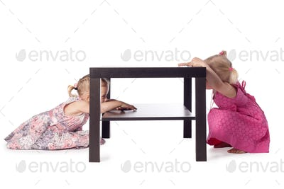 two little girls hiding behind table